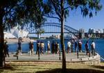 Tourists at Mrs. Macquarie's Chair with view of Sydney Opera House and Harbour Bridge