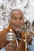 Spectator in traditional dress (gho) with prayer wheel and beads at the Paro Tsechu (festival)