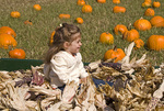 Child posing in a wagon with corn husks during the Half Moon Bay (California) Art and Pumpkin Festival