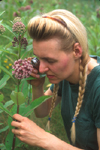 LADY USING MAGNIFIER TO LOOK AT MILKWEED FLOWERS