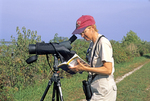 LADY WITH SPOTTING SCOPE AND BIRD FIELD GUIDE