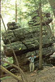 MAN AT ROCK FORMATION AT COOPERS ROCK STATE FOREST IN WV