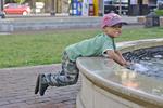 Boy having fun playing in water fountain