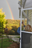 Lady taking photo of rainbow from doorway