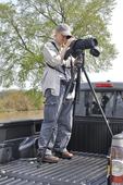 Lady spotting birds using a spotting scope on a tripod from the back of a pick-up truck