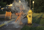Kids playing at open fire hydrant
