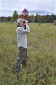 Lady watching birds through binoculars