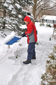Lady dressed in winter clothing shoveling snow from walkway