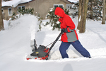Lady dressed in winter clothing using snowblower