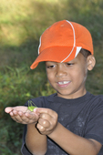 Boy holding a katydid he just caught.