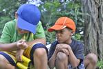 Two boys looking at a katydid.