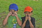 Two boys holding black walnut shells in front of their noses to look like 'pig' noses.