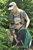 Lady and boy using binoculars as a magnifyer to look at Rhododendron flower