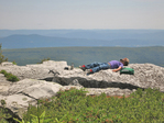Boy resting on large rock along the Allegheny Front mountains after a day of hiking