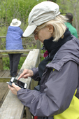Lady birdwatcher texting about birds and bird locations