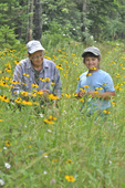 Grandmother and granddaughter looking at Black-eyed Susan flowers