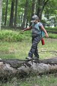 Young girl balancing herself as she walks on a log