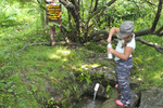 Young girl filling water bottle a a cold mountain spring