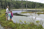 Mother and daughter standing on beaver dam looking at the beaver lodge
