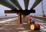 Overhead pipes on an artificial causeway carry oil from Endicott Field on the Arctic Ocean.