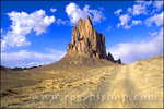 Afternoon light on Shiprock and dirt road under blue sky and clouds