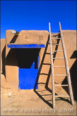 Ladder and adobe house with blue door, South House