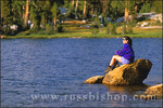 Woman sitting on a rock along the shore of Boothe Lake in the Cathedral Range