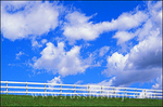Clouds in blue sky above white fence and green grass in upper Ojai Valley, Ojai, California