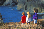 Mother and kids watching the surf from a bluff along US Highway 1 on the Pacific coast, Big Sur, California
