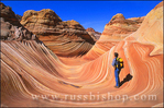 "Hiker on the swirling sandstone formation known as ""The Wave"" in the Coyote Buttes area, Paria Canyon-Vermilion Cliffs Wilderness, Arizona"