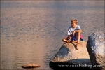 Boy fishing from a rock on the shore of Budd Lake, Tuolumne Meadows, Yosemite National Park, California