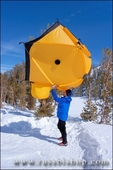 Skier shaking out a Yellow dome tent in a backcountry ski camp in Little Lakes Valley, Inyo National Forest, Sierra Nevada Mountains, California