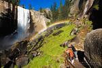 Hikers on the Mist Trail enjoying a rainbow under Vernal Fall, Yosemite National Park, California USA