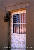 American flag in the door of an adobe house, Taos Pueblo, New Mexico