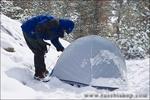 Snow falling on backpacker and tent at Gem Lake, John Muir Wilderness, Sierra Nevada Mountains, California