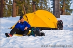 Backcountry skier (talking on a radio) and yellow dome tent, Yosemite National Park, California