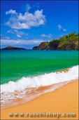 Surf, sand and blue green waters at Secret Beach (Kauapea Beach), Kilauea Lighthouse visible, Island of Kauai, Hawaii