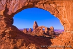 Morning light on Turret Arch through North Window (hiker visible), Arches National Park, Utah