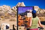 Interpretive sign and visitor at the trailhead to Barker Dam, Joshua Tree National Park, California