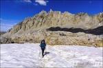 Backpacker crossing snowfield on the Bishop Pass Trail, John Muir Wilderness, Sierra Nevada Mountains, California USA