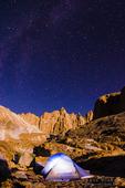 Tent and moon lit Sierra crest under starry night sky, John Muir Wilderness, California USA