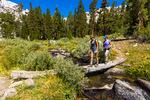 Hikers crossing footbridge in the Big Pine Lakes basin, John Muir Wilderness, California USA