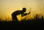 A bushman, or san, crouches while hunting wildebeeste. He is holding a bow and arrow at the ready and is seen silhoutted against the setting sun.