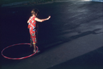 USA,Illinois, young child with a hula hoop casts a long shadow.