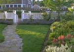 Small enclosed front yard with perennial borders, roses, stone path to front door.