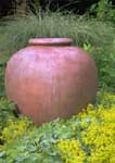 Decorative terracotta jar in perennial garden.