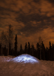 North America, USA, Alaska, near Fairbanks, quinzhee snow shelter lit from inside, night sky and stars