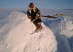 Inuit atop igloo