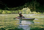 Local girl kayaks into shallow cave in the Rock Islands of Palau, Micronesia.