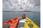 Local girl on skiff with kayaks. Rock Islands, Palau, Micronesia.